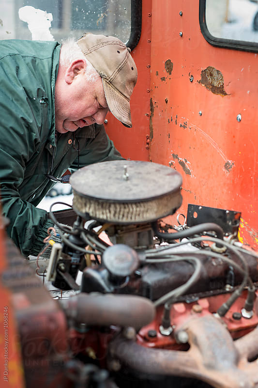 Overweight Man Auto Mechanic Farmer Repairing Old Engine on Rusty Farm Machenery by JP Danko for Stocksy United