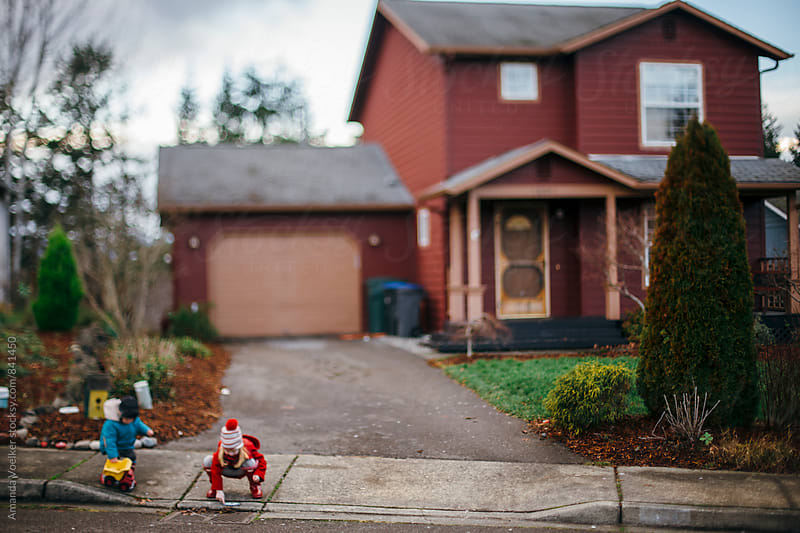 Two Young Children Play in front of their Red House by Amanda Voelker for Stocksy United