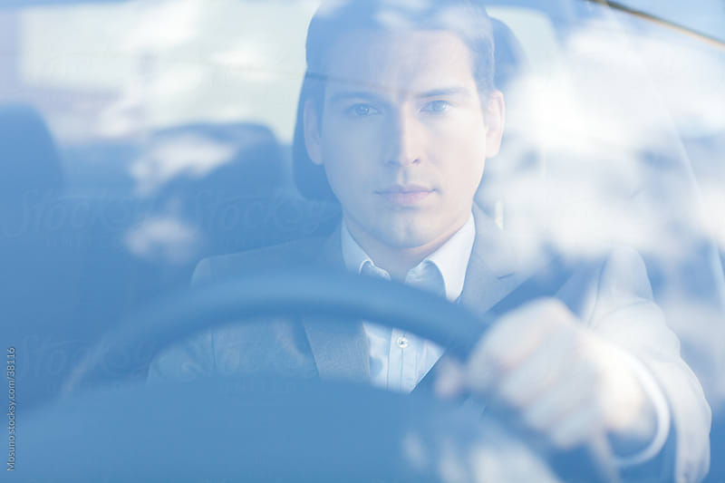 Young businessman driving a car. by Mosuno for Stocksy United