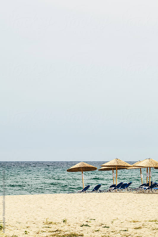 Minimalist seascape - greek beach with umbrellas by Aleksandar Novoselski for Stocksy United