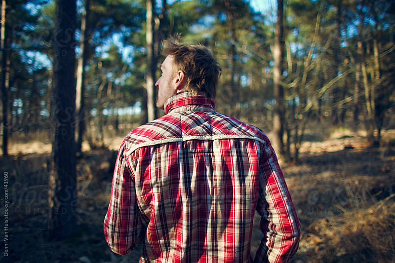 Young man walks around in a forest wearing a checkered shirt by Denni Van Huis for Stocksy United