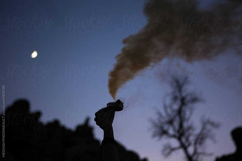Silhouette of Hand Holding Yellow Smoke Bomb  by MEGHAN PINSONNEAULT for Stocksy United
