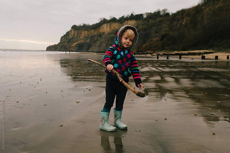 Little girl carrying  a big stick on a deserted wet beach in winter. by Julia Forsman for Stocksy United