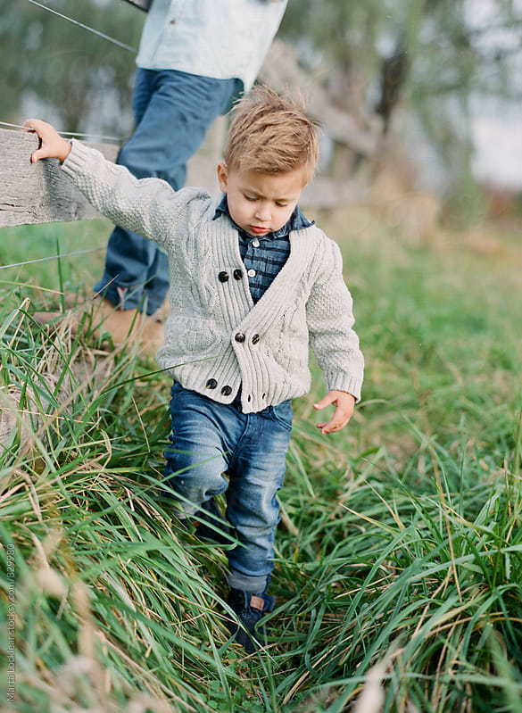 Young boy in a grey sweater by Marta Locklear for Stocksy United