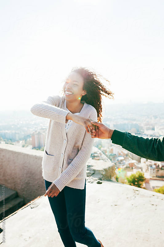 Happy young woman dancing with her boyfriend above city. by BONNINSTUDIO for Stocksy United