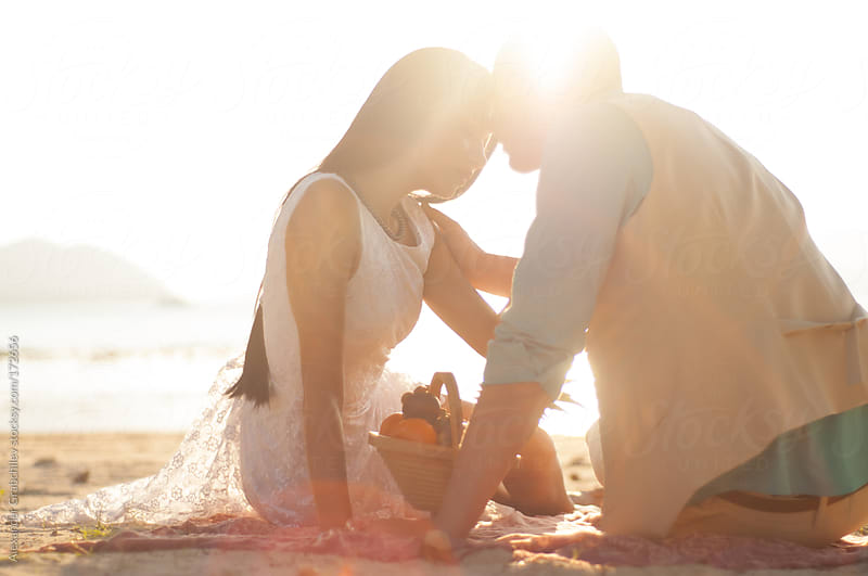 Loving Couple At The Beach In Sunset Light by Alexander Grabchilev for Stocksy United