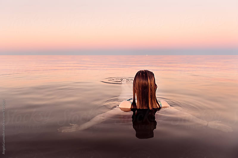 Girl in shallow calm water relaxes at dusk by Angela Lumsden for Stocksy United