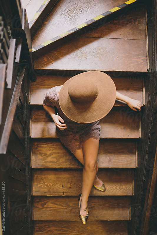 Girl sitting on wood stairs in wide brim hat by Gabrielle Lutze for Stocksy United