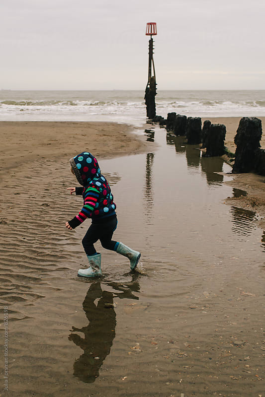 Small child and her reflection running through water next to a sea barrier on a wintry beach. by Julia Forsman for Stocksy United