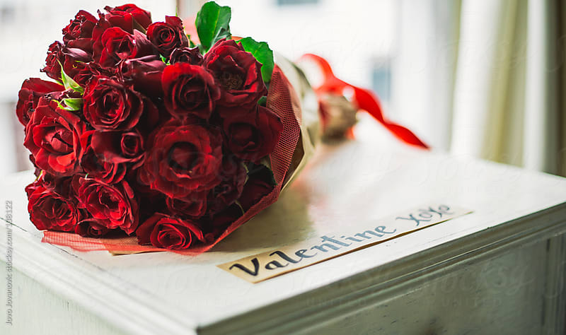 Bouquet of red roses sitting next to a valentine sign. by Jovo Jovanovic for Stocksy United
