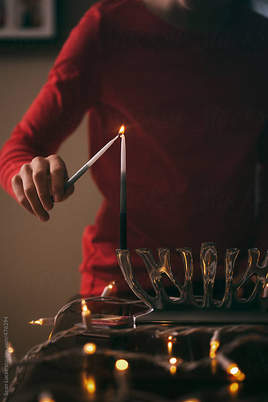 Hanukkah: Lighting Candles On The First Night Of Hanukkah by Sean Locke for Stocksy United