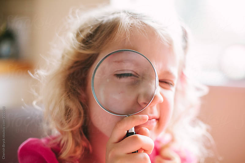 A girl holds a magnifying glass up to her face. by Cherish Bryck for Stocksy United