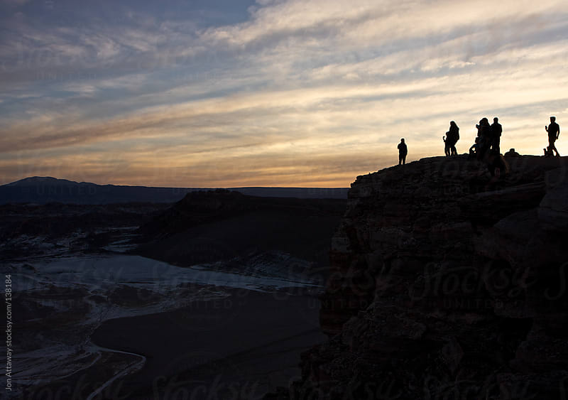 Silhouettes of people on a clifftop by Jon Attaway for Stocksy United