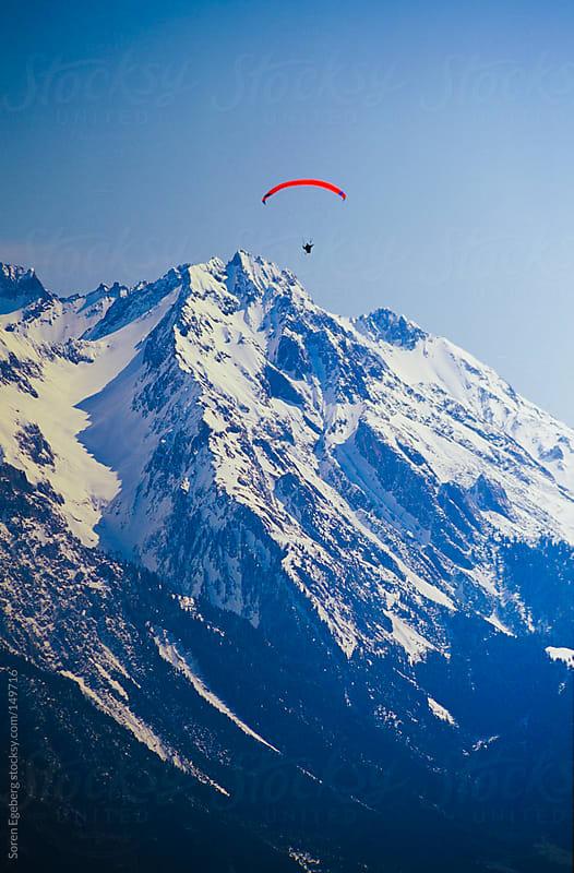 Paraglider flying in winter mountain landscape by Soren Egeberg for Stocksy United