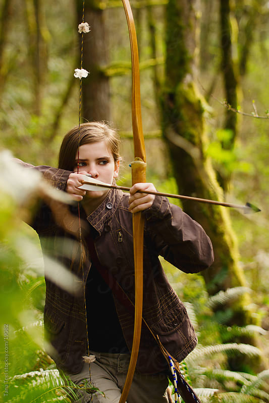 Young girl taking aim with bow and arrow by Tana Teel for Stocksy United