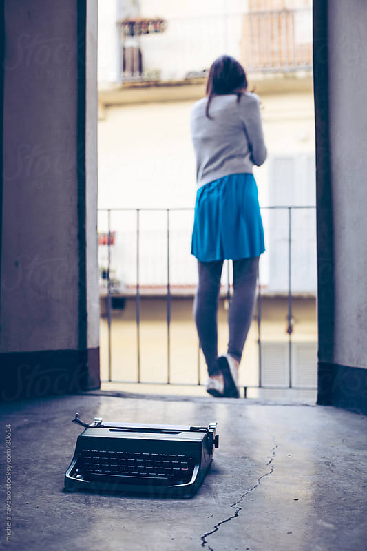 Typewriter on the floor with a girl on background by michela ravasio for Stocksy United