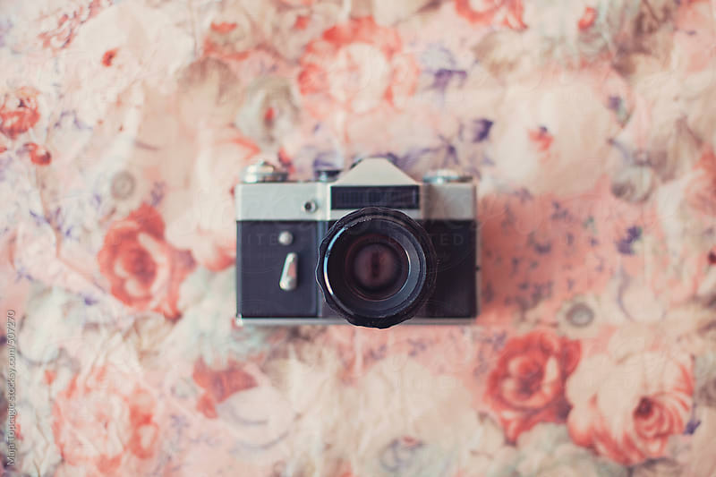 Old vintage retro film camera on a floral background by Maja Topcagic for Stocksy United