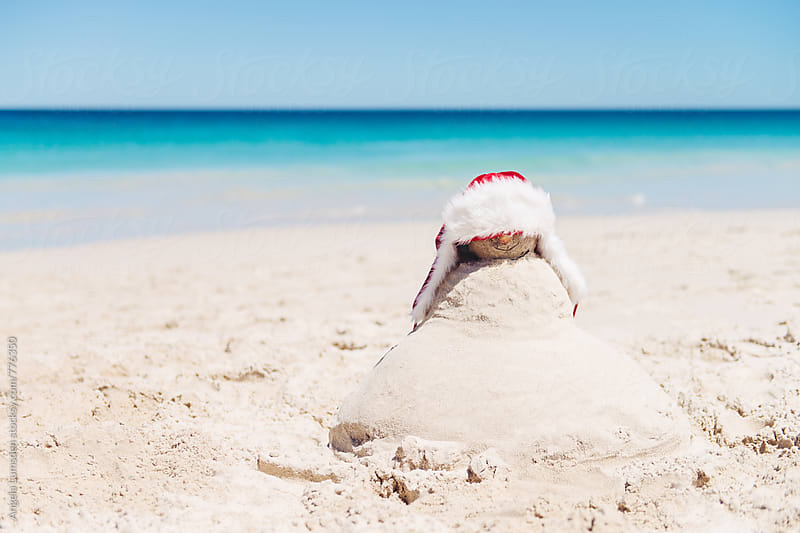 Sand snowman at the beach at Christmas in Australia by Angela Lumsden for Stocksy United