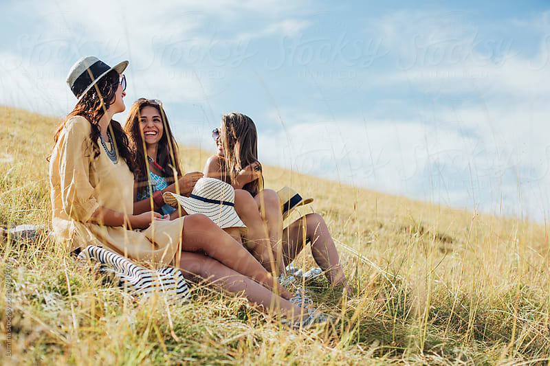 Three Young Women Sitting on the Grass  by Lumina for Stocksy United
