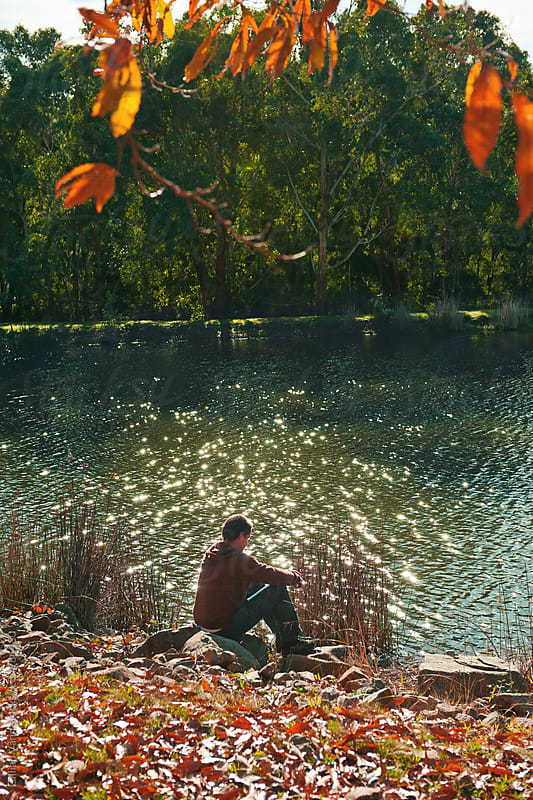 man sitting by a lake, fall by Gillian Vann for Stocksy United