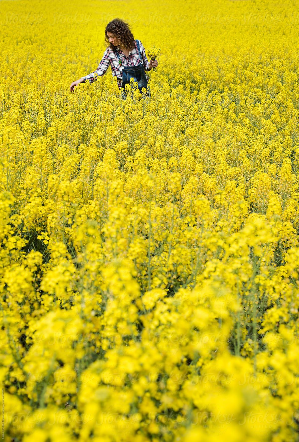 Woman In A Field Of Yellow Flowers Stocksy United