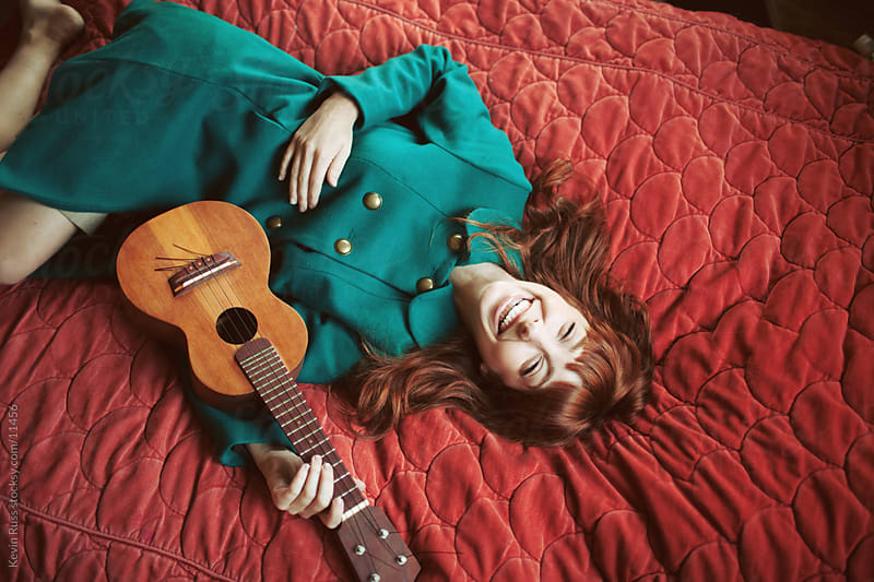 Happy Ukulele Woman on Bed by Kevin Russ for Stocksy United