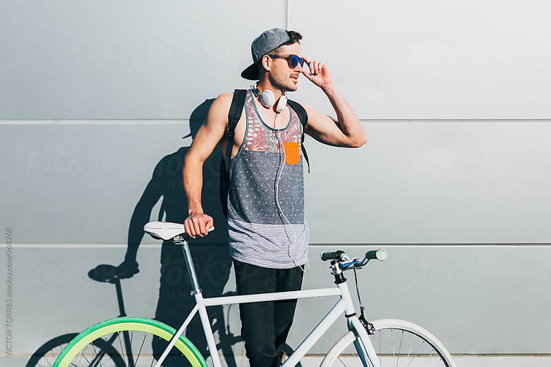 Young Sexy Man with a Bicycle Leaning on a Metallic Wall