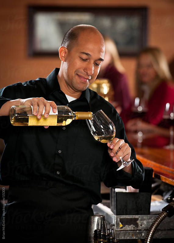 Bartender pours a glass of white wine. by Brian McEntire for Stocksy United