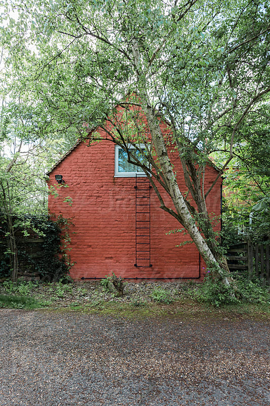 Orange gable end of a house. Fire escape leading from top window. by Paul Phillips for Stocksy United