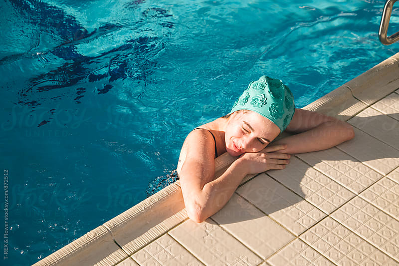 smiling young woman in green cap in swimming pool by Danil Nevsky for Stocksy United