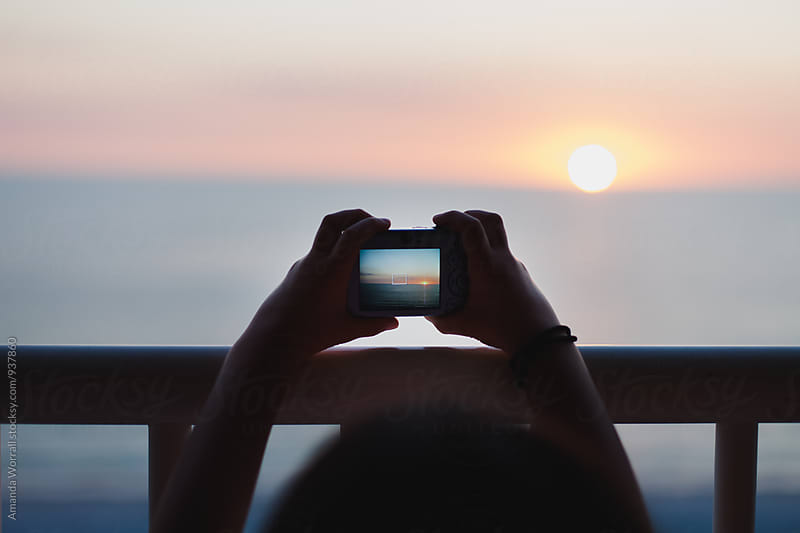 Silhouette of a child's hands holding a camera up to take a photo of the sunset at the beach by Amanda Worrall for Stocksy United