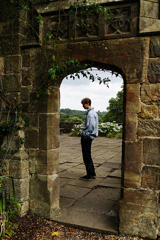 Male model seen through garden archway. by Julia Forsman for Stocksy United