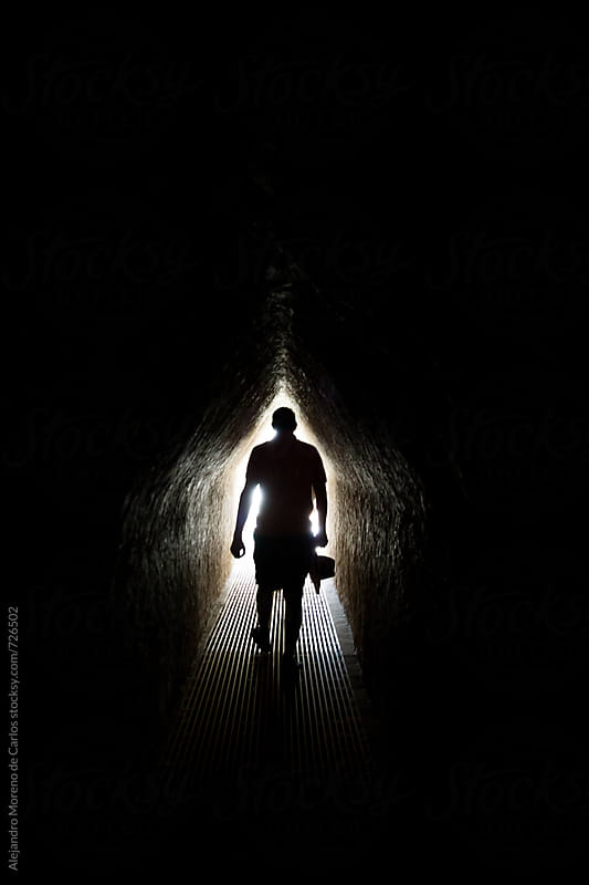 Silhouette of a man walking through an underground tunnel by Alejandro Moreno de Carlos for Stocksy United