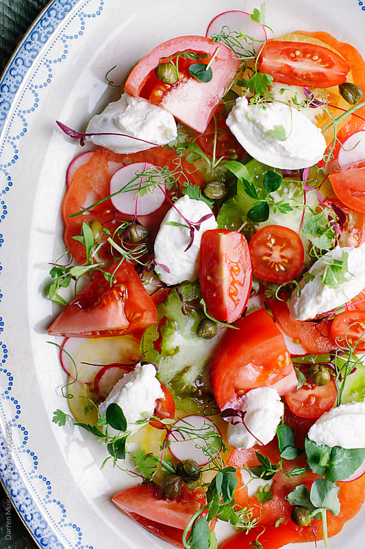 Closeup of a tomato salad. by Darren Muir for Stocksy United