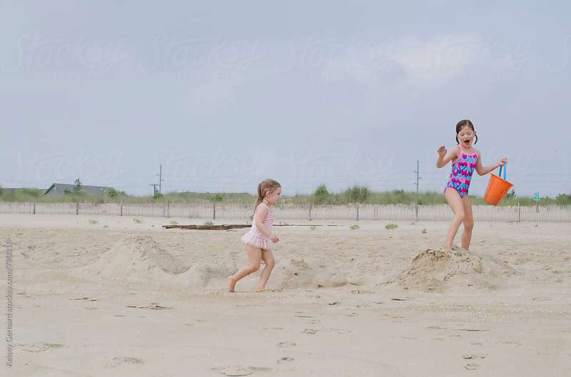 Two sisters run and play on a sandy beach dune. by Kelsey Gerhard for Stocksy United