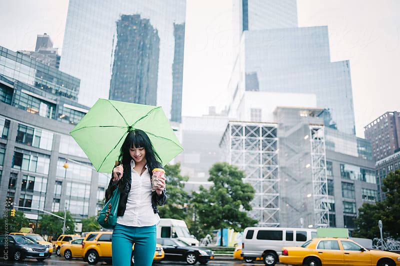 Happy woman walking under the rain, NYC by GIC for Stocksy United