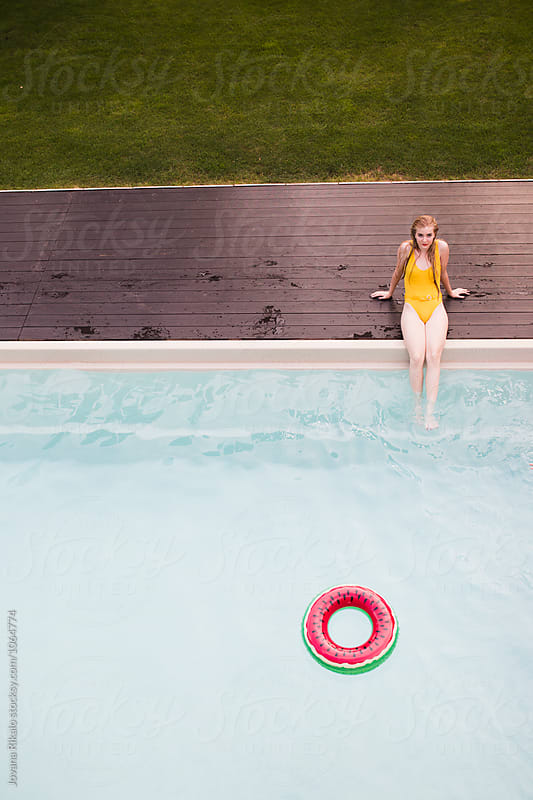 Young woman sitting by the pool by Jovana Rikalo for Stocksy United