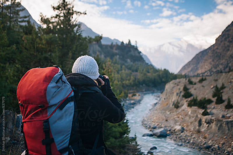 A young backpacker photographing in the mountains by Shikhar Bhattarai for Stocksy United