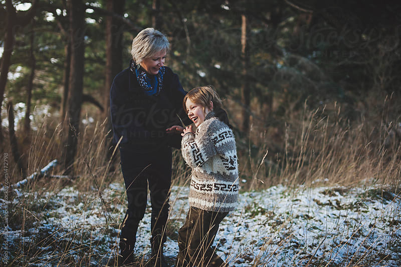 Happy grandma enjoying her grandchild outside in winter - tickling fun by Rob and Julia Campbell for Stocksy United