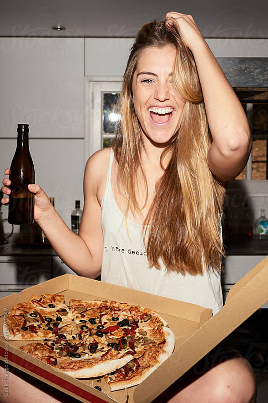 blonde young woman eating pizza by Guille Faingold for Stocksy United