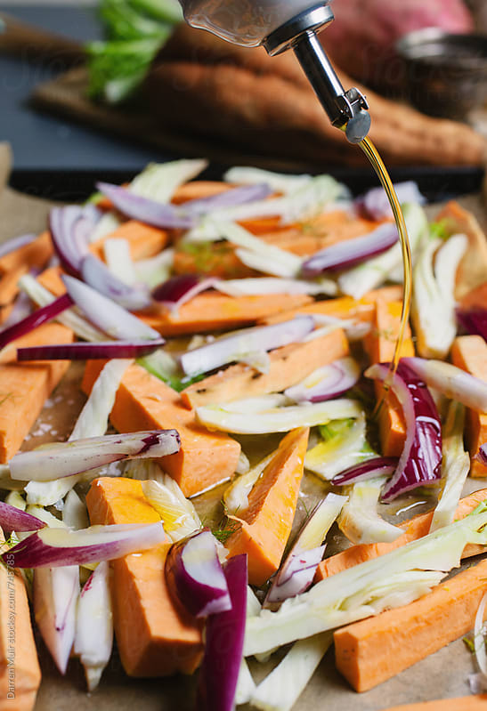 Sweet potato,fennel,red onion and garlic on a tray be drizzled with olive oil. by Darren Muir for Stocksy United