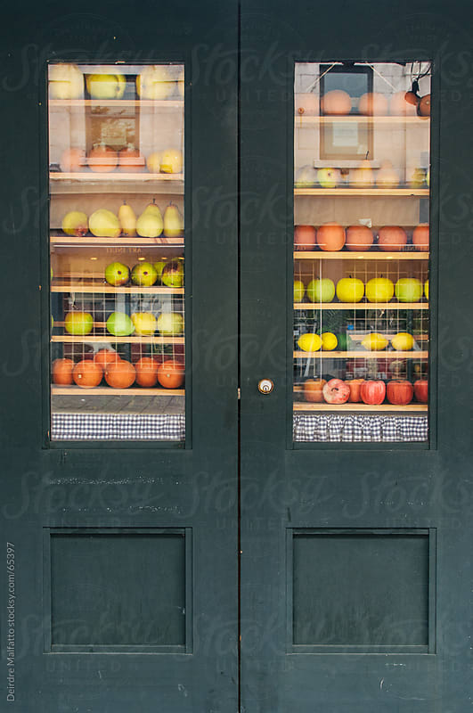 Various fruit on shelves in the windows of a door by Deirdre Malfatto for Stocksy United
