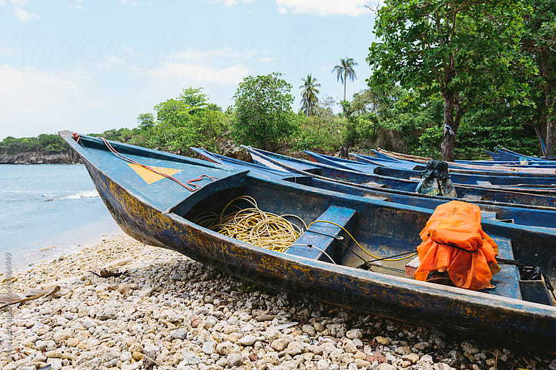 Several blue fishing boats on rocky shore by Trent Lanz for Stocksy United