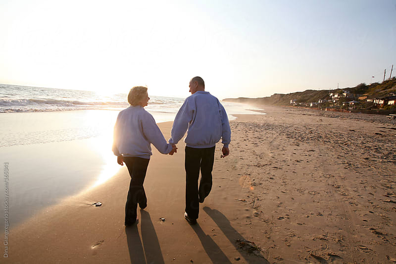Elderly couple holding hands and walking on the beach by Dina Giangregorio for Stocksy United