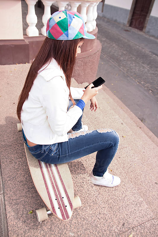 Young woman sitting on a skate and using a phone by Nataša Mandić for Stocksy United