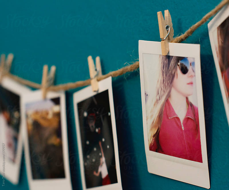 Horizontal view of mini polaroids clipped to a string on a wall by Tana Teel for Stocksy United