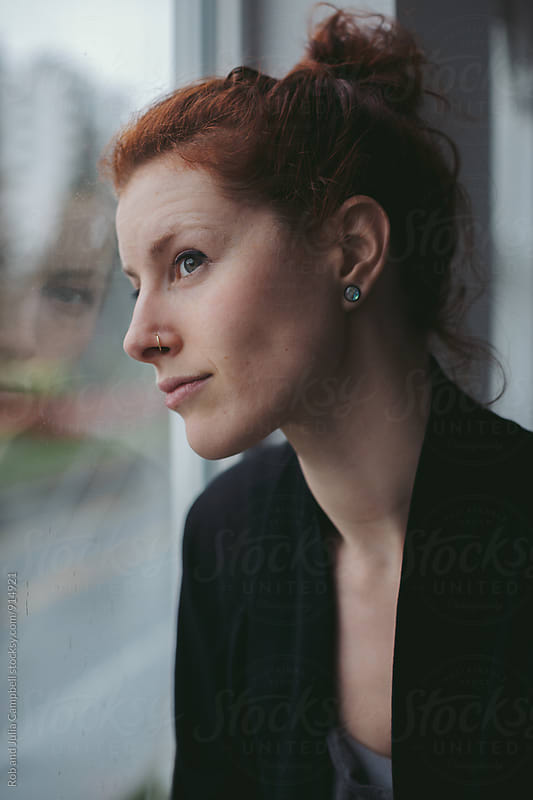 Young, thoughtful caucasian woman sitting near window on rainy day by Rob and Julia Campbell for Stocksy United
