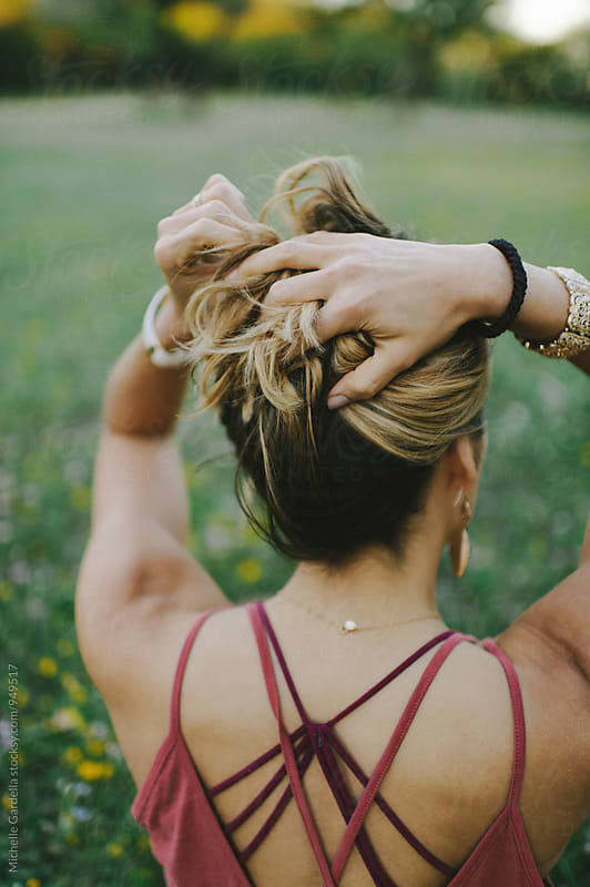 Girl Holding Up Hair by Michelle Gardella for Stocksy United