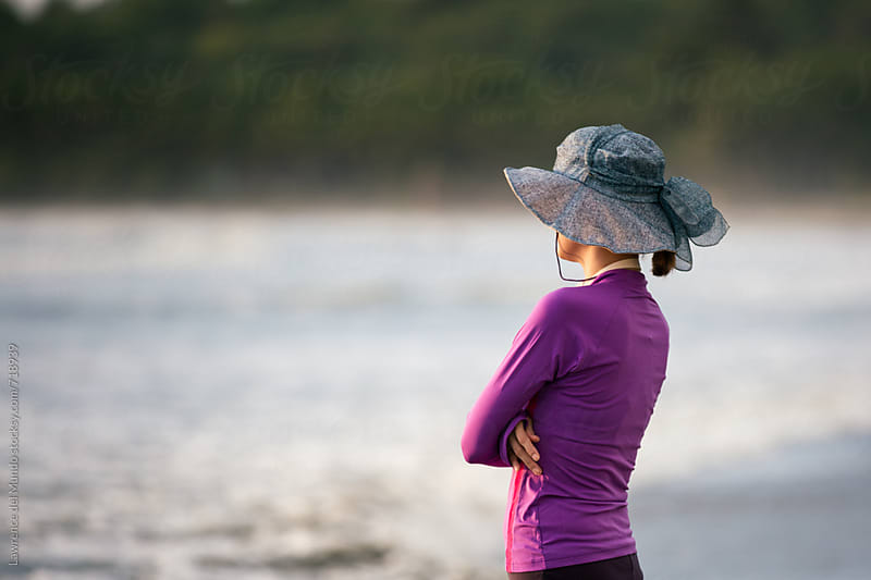 A mother wearing swimsuit and hat stylishly waits for her sons to finish swimming in the sea.  by Lawrence del Mundo for Stocksy United