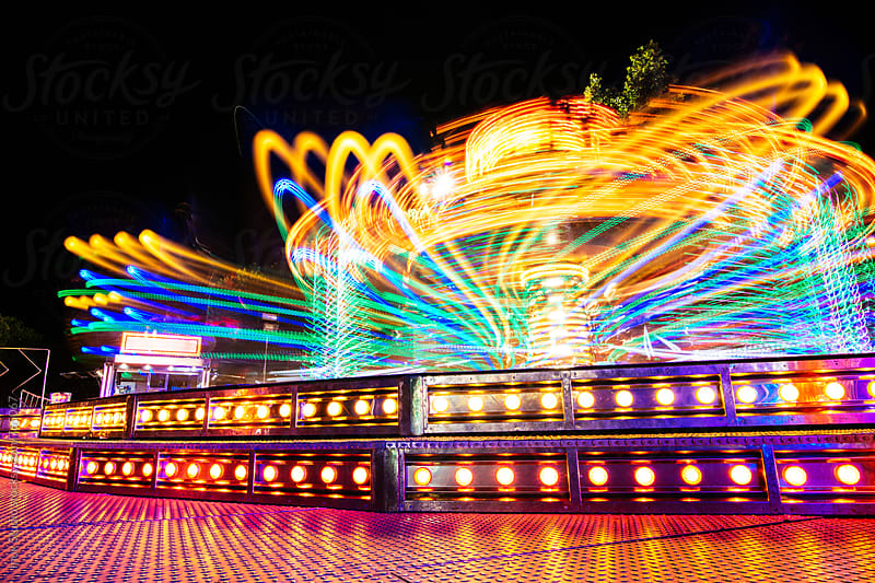 Long exposure shot of carousel attraction in a fair at night with colorful lights by Inuk Studio for Stocksy United